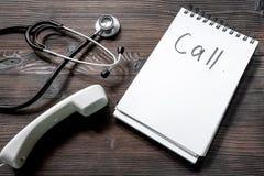 As palavras chamam escrito em um caderno perto do phonendoscope e o telefone ajustou na opinião de madeira escura do desktop Fotografia de Stock Royalty Free