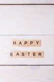 As palavras da Páscoa feliz são escritas em cubos de madeira Conceito feliz da Páscoa no fundo de madeira branco imagens de stock royalty free