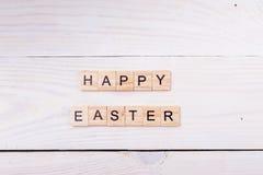 As palavras da Páscoa feliz são escritas em cubos de madeira Conceito feliz da Páscoa no fundo de madeira branco fotografia de stock royalty free
