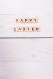 As palavras da Páscoa feliz são escritas em cubos de madeira Conceito feliz da Páscoa no fundo de madeira branco imagem de stock royalty free
