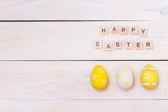 As palavras da Páscoa feliz são escritas em cubos e em ovos de madeira Conceito feliz da Páscoa no fundo de madeira branco fotos de stock royalty free