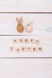 As palavras da Páscoa feliz são escritas em cubos e em ovos de madeira Conceito feliz da Páscoa no fundo de madeira branco foto de stock