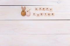 As palavras da Páscoa feliz são escritas em cubos e em ovos de madeira Conceito feliz da Páscoa no fundo de madeira branco imagem de stock