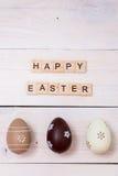 As palavras da Páscoa feliz são escritas em cubos e em ovos de madeira Conceito feliz da Páscoa no fundo de madeira branco fotos de stock