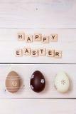 As palavras da Páscoa feliz são escritas em cubos e em ovos de madeira Conceito feliz da Páscoa no fundo de madeira branco foto de stock royalty free