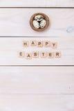As palavras da Páscoa feliz são escritas em cubos e em ovos de madeira Conceito feliz da Páscoa no fundo de madeira branco imagem de stock royalty free