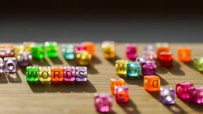 As palavras da palavra dobraram-se de um quadrado de blocos coloridos em uma superfície de madeira Fotografia de Stock Royalty Free