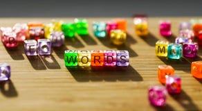 As palavras da palavra dobraram-se de um quadrado de blocos coloridos em uma superfície de madeira Foto de Stock