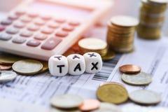 As palavras e a calculadora do imposto empilharam moedas no papel da conta da fatura para o enchimento do imposto do tempo imagens de stock royalty free