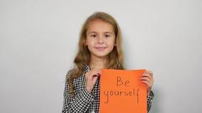 As palavras escritas à mão sejam você mesmo da exibição feliz da menina na folha alaranjada video estoque