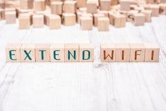 As palavras estendem WIFI formado por blocos de madeira em uma tabela branca fotos de stock