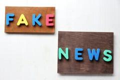 As palavras FALSIFICAM AS NOTÍCIAS feitas das letras no fundo de madeira fotos de stock
