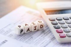 As palavras pagas e o papel da conta da fatura da calculadora pelo tempo pagaram o pagamento em finanças do negócio do escritório foto de stock royalty free