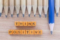 As palavras pensam o positivo na tabela de madeira com grupo de lápis imagem de stock