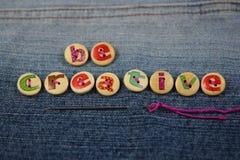 As palavras sejam criativas soletradas com botões indicados por letras Imagens de Stock