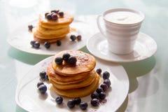 As panquecas do café da manhã na placa à moda serviram com mirtilos frescos e cobriram com xarope de bordo original, copo seguint fotografia de stock royalty free