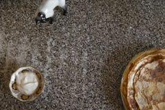 As panquecas do queijo com creme de leite kithcen sobre a tabela e uma estátua da porcelana do gato imagens de stock royalty free