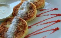 As panquecas do queijo creme serviram na placa com doce e creme de leite de morango Fotografia de Stock