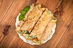 As panquecas encheram-se com os espinafres e o queijo na superfície de madeira Fotografia de Stock