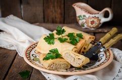 As panquecas enchidas do russo rolam com carne na bacia tradicional da argila no fundo de madeira Imagem tonificada Foco seletivo imagens de stock