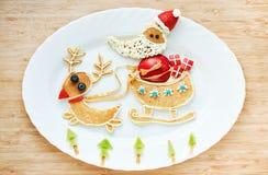As panquecas engraçadas Santa Claus e a rena montam em um trenó, criam Imagem de Stock