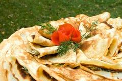 As panquecas frescas decoradas com tomate levantaram-se Fotos de Stock Royalty Free