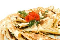 As panquecas frescas decoradas com tomate levantaram-se no branco Imagem de Stock Royalty Free