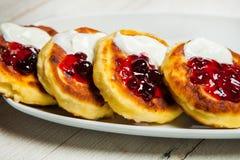 As panquecas tradicionais do requeijão do syrniki do russo tomam o café da manhã na placa Bolos de queijo do russo com passas em  Imagem de Stock Royalty Free