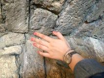 As paredes da cidade e a mão velhas da mulher foto de stock royalty free