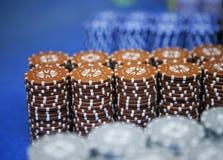 As partes coloridas do jogo das microplaquetas de pôquer encontram-se na tabela de jogo na pilha Foto de Stock Royalty Free
