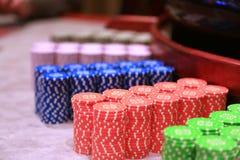 As partes coloridas do jogo das microplaquetas de pôquer encontram-se na tabela de jogo na pilha Imagens de Stock Royalty Free