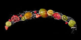 As partes de fruto na água espirram, isolado no fundo preto fotos de stock