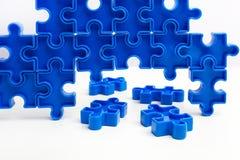 As partes de um enigma de serra de vaivém azul arranjaram para formar uma página no fundo branco Barreiras da ruptura junto para  Fotografia de Stock