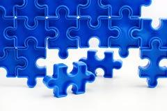 As partes de um enigma de serra de vaivém azul arranjaram para formar uma página no fundo branco Barreiras da ruptura junto para  Foto de Stock