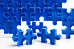 As partes de um enigma de serra de vaivém azul arranjaram para formar uma página no fundo branco Barreiras da ruptura junto para  Imagem de Stock