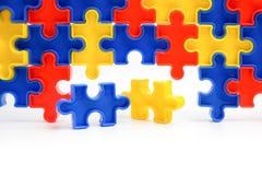 As partes de um enigma de serra de vaivém colorido arranjaram para formar uma página no fundo branco Barreiras da ruptura junto p Imagens de Stock