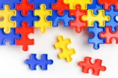 As partes de um enigma de serra de vaivém colorido arranjaram para formar uma página no fundo branco Barreiras da ruptura junto p Foto de Stock Royalty Free