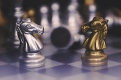 As partes de xadrez knights enfrentar-se para um suporte isolador Cavaleiros da xadrez que confrontam-se fotos de stock royalty free