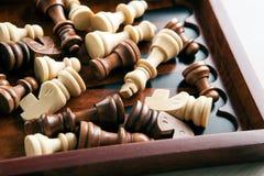 As partes de xadrez de madeira encontram-se em uma placa de xadrez Imagens de Stock