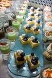 As partes do bolo de queijo dos mirtilos arranjaram na bandeja de vidro na sobremesa Imagem de Stock