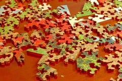 As partes do enigma espalharam através de uma tabela de madeira escura Imagens de Stock Royalty Free