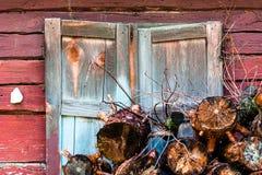 As partes molhadas de árvores velhas abatidas de espécies diferentes são à casa da quinta de madeira da janela fechado dos obtura Fotografia de Stock
