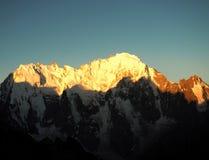 As partes superiores das montanhas são iluminadas pelo sol da manhã Fotografia de Stock Royalty Free