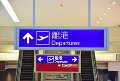 As partidas assinam dentro Hong Kong International Airport com caráteres chineses Fotografia de Stock Royalty Free