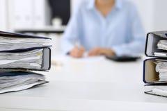 As pastas com papéis estão esperando para ser processadas para trás pela mulher de negócio ou pelo guarda-livros no borrão Audito fotografia de stock