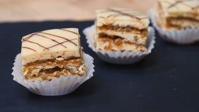 As pastelarias doces minúsculas das mostras de um macro do close-up endurecem bolos da pastelaria, bolos com creme branco e enchi filme