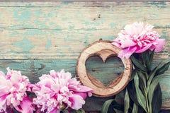 As peônias e o coração cor-de-rosa cinzelaram na madeira no grunge velho pintado Imagens de Stock