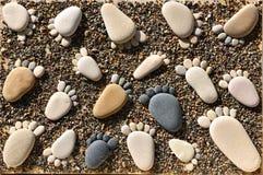 As pedras do seixo arranjaram como pegadas na praia imagem de stock royalty free