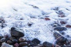 As pedras e o mar coloridos diferentes de brilho brilhantes molhados do seixo espumam Imagens de Stock