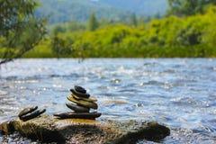 As pedras em um rio da floresta dobraram-se em uma figura imagens de stock